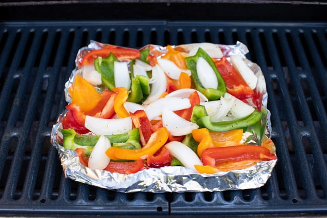 sliced bell peppers with onions in a homemade tin foil grill basket on a grill grate