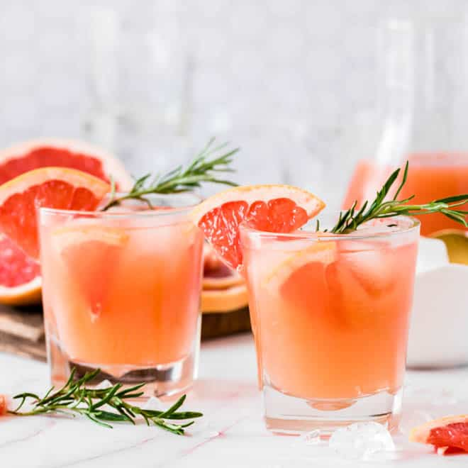 two glasses of grapefruit gin fizz sitting on a white table with grapefruit and rosemary sprigs on the side