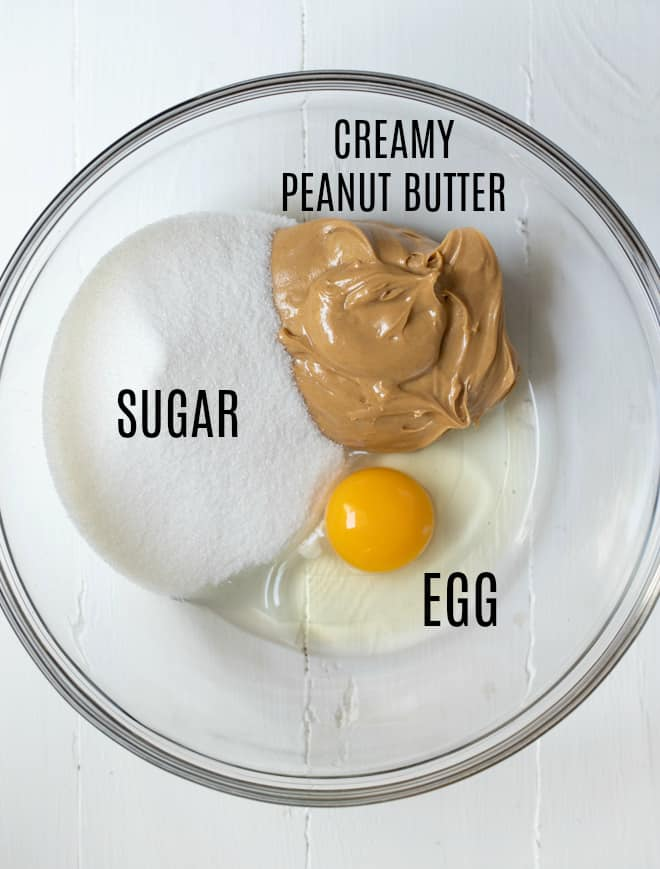 creamy peanut butter, egg and sugar in a glass bowl on a white counter