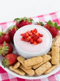 a bowl filled with strawberry cheesecake dip sitting on a plate with graham crackers and whole strawberries