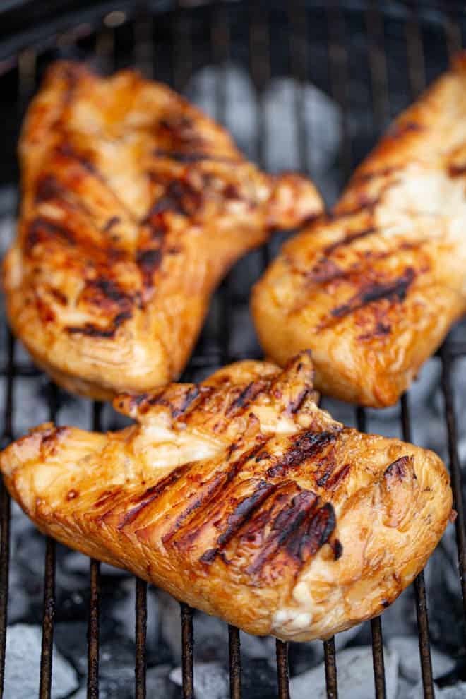 three pieces of teriyaki chicken on a grill