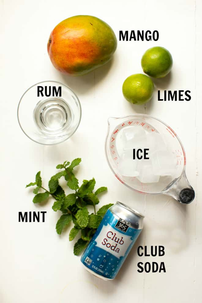 ingredients for mango mojito including mango, two limes, rum, ice, mint and club soda on a white table