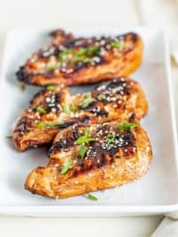 three pieces of grilled teriyaki chicken sitting on a white plate and garnished with sesame seeds and chives