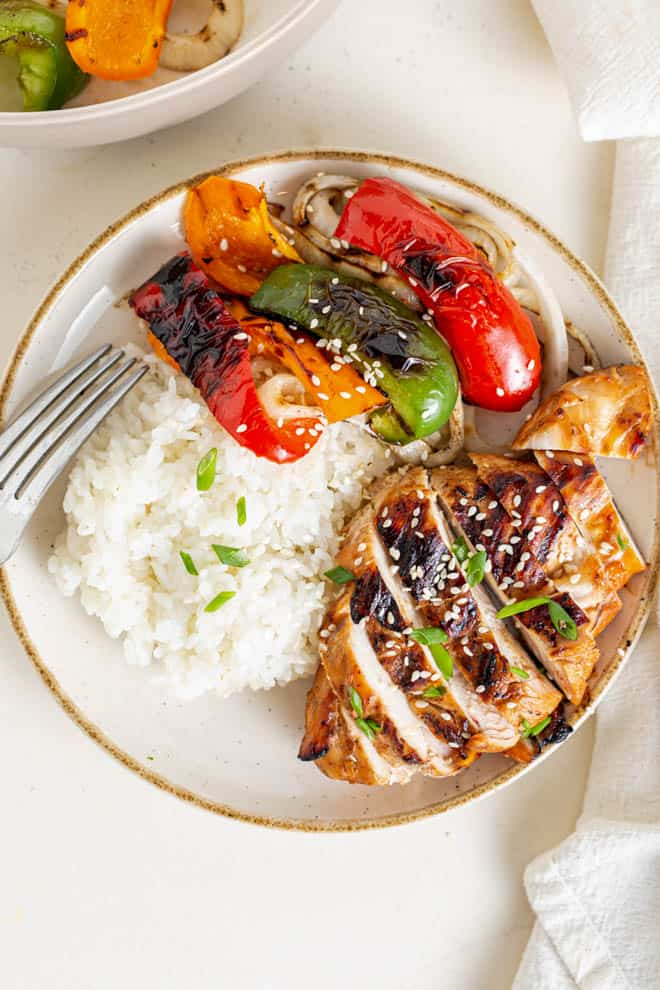 teriyaki chicken on a plate with sliced grilled peppers and rice.