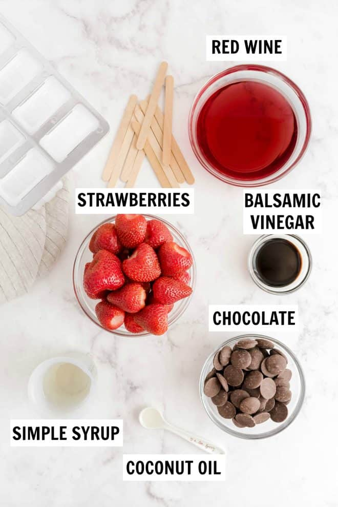 ingredients to make strawberry red wine popsicles sitting on a counter