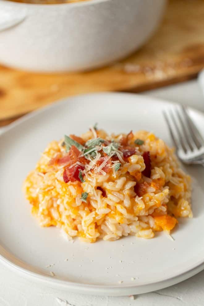 butternut squash risotto with sage and bacon on a white plate