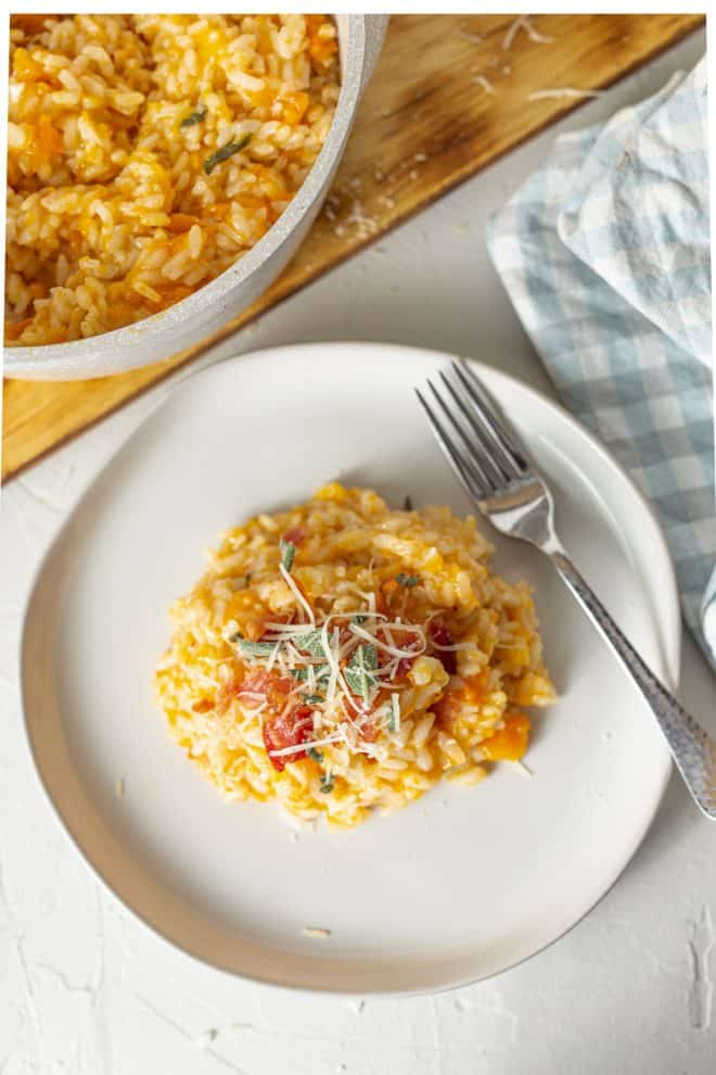 butternut squash risotto on a white plate sprinkled with fresh parmesan and sage