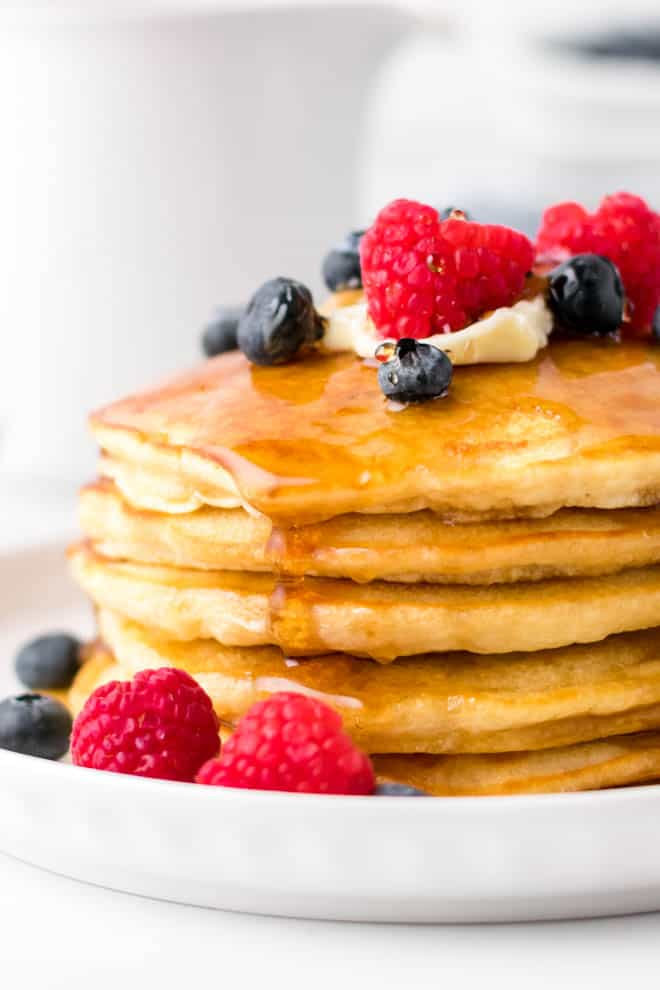 a stack of fluffy homemade pancakes on a white plate with butter, syrup and berries