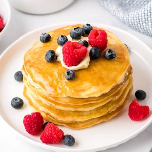 a stack of four fluffy homemade pancakes on a white plate with butter, syrup, blueberries and raspberries