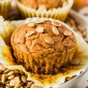 one pumpkin muffin sitting on a plate with pumpkin seeds on top
