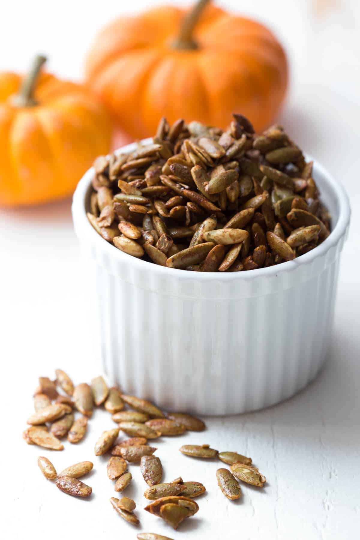 a bowl filled with oven roasted pumpkin seeds with a few scattered on a the counter next to the bowl