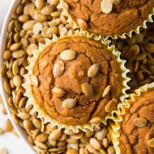 three vegan pumpkin muffins sitting on top of pepitas