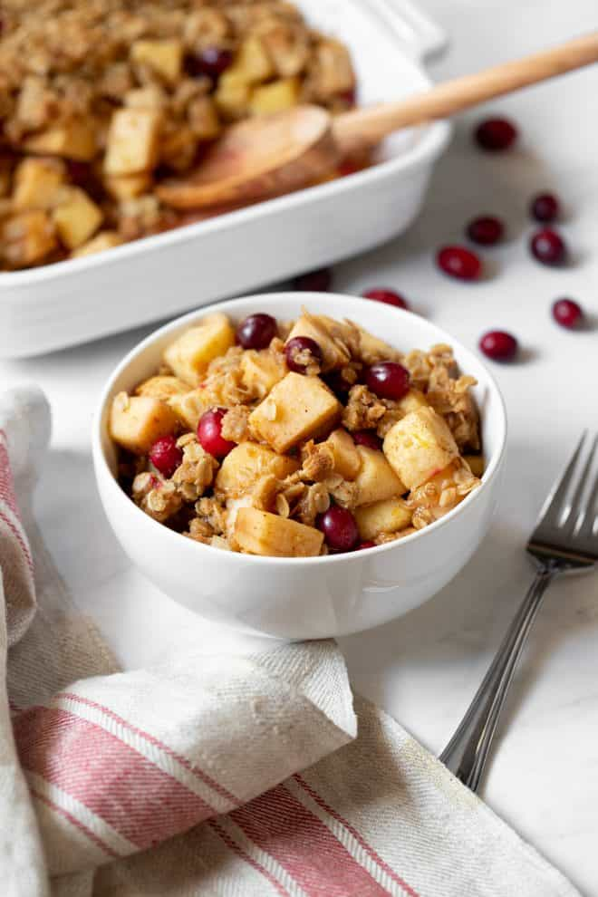 a bowl of apple, pear and cranberry crisp sitting on a table with a fork on the side