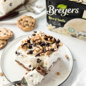 a slice of chocolate chip cookie ice cream cake on a white plate with a fork