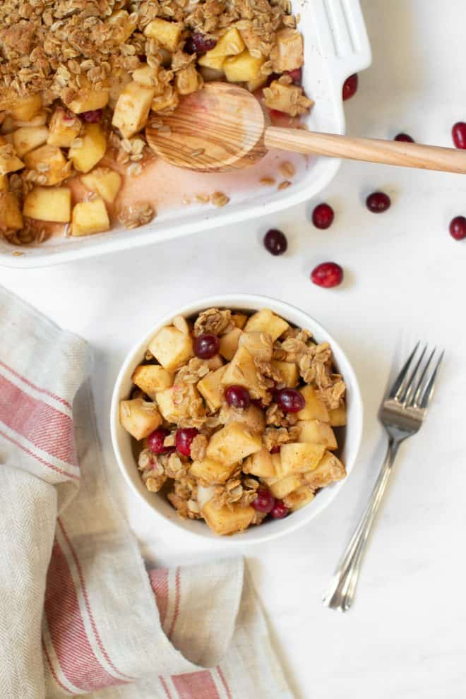 a bowl of apple pear cranberry crisp sitting on a white table with a napkin on the side