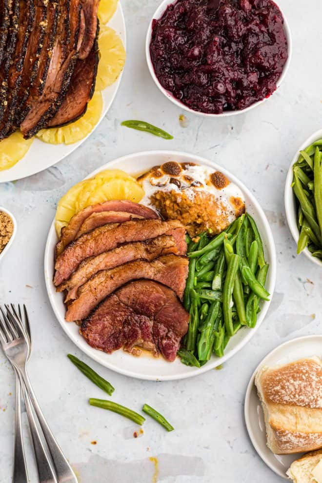 maple glazed ham served on a plate with green beans and sweet potato casserole