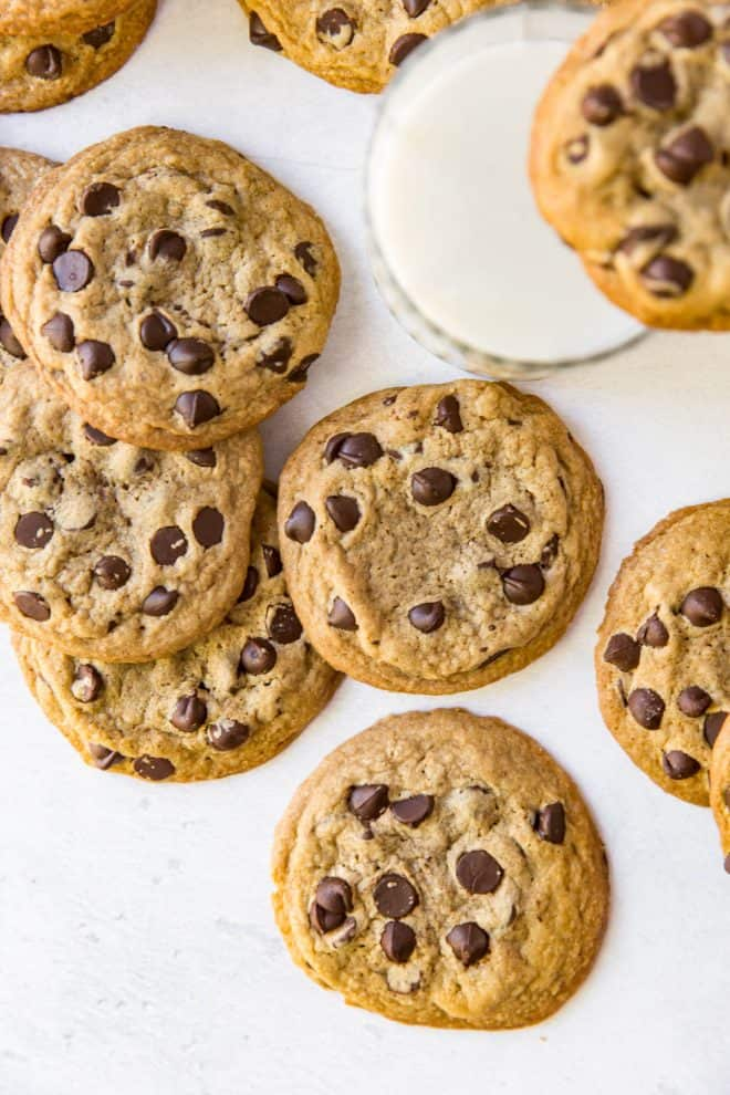 a pile of chocolate chip cookies on a white table