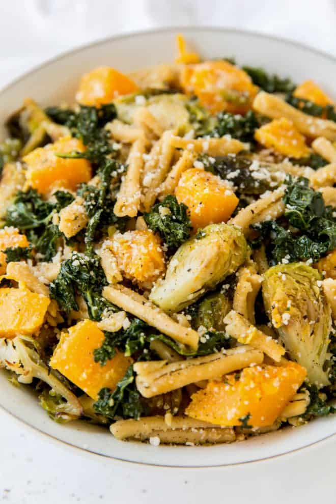 a close up photo os a bowl of pasta with brussels sprouts, butternut squash and kale