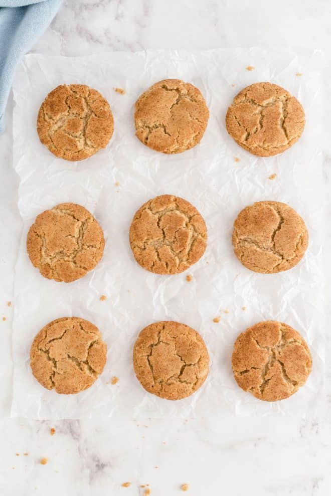 nine brown butter snickerdoodles sitting on a piece of white parchment paper