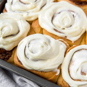 baked cinnamon rolls in a metal tin with cream cheese frosting on top