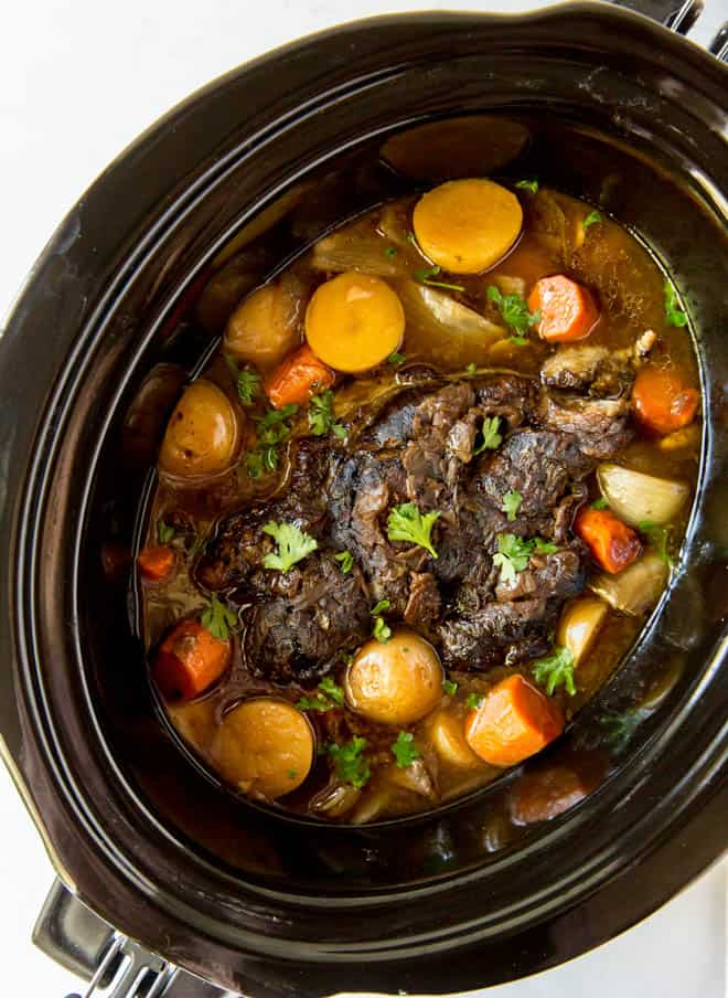 cooked pot roast with potatoes and carrots in a slow cooker