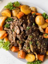 pot roast with potatoes and carrots on a white plate