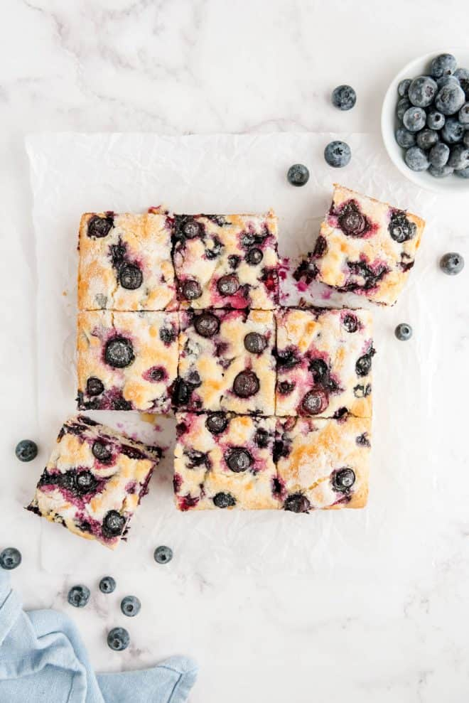 blueberry breakfast cake cut into nine slices on a piece of white parchment paper