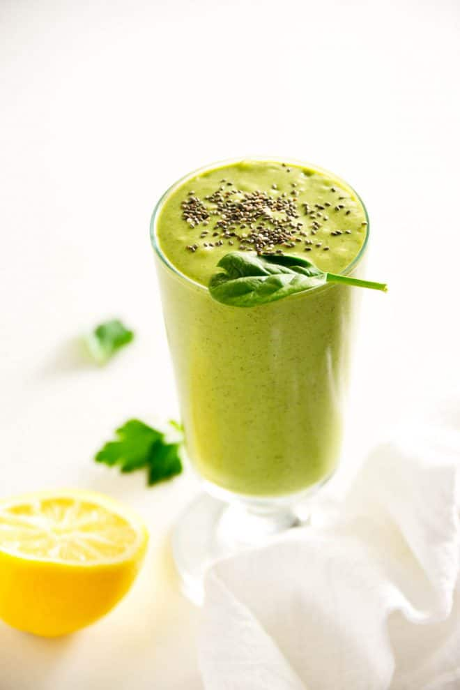 green detox smoothie in a glass cup with chia seeds sprinkled on top