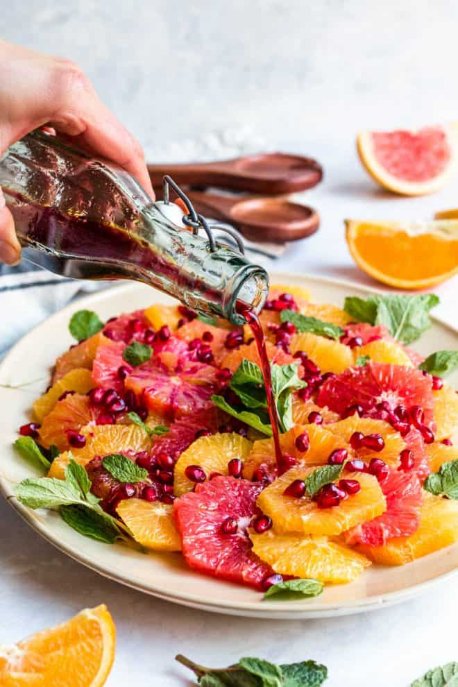 citrus salad on top of a plate with dressing poured over it