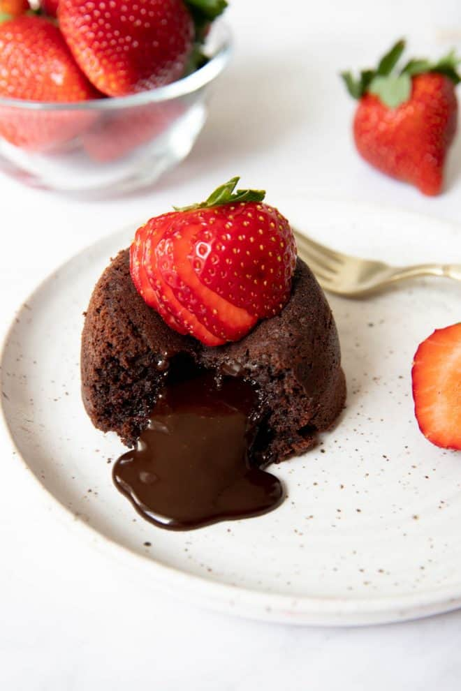 one lava cake sitting on a white plate with a sliced strawberry on top