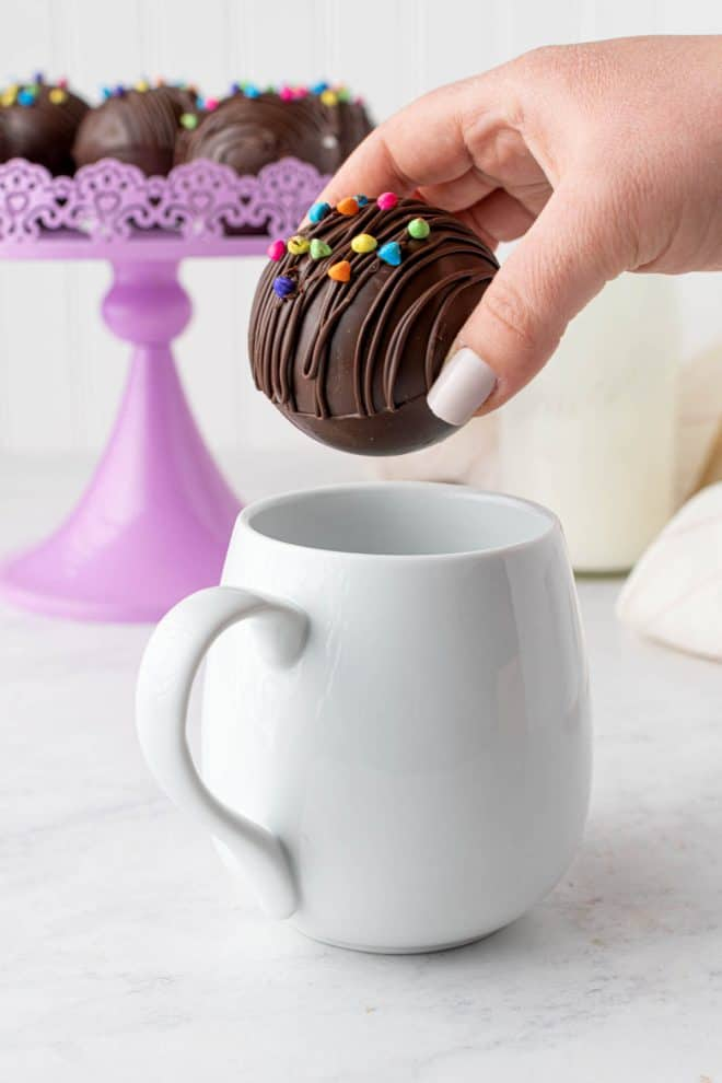 dropping one hot chocolate ball into a mug before filling with hot milk