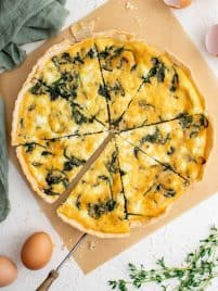 a spinach and feta quiche cut into 8 slices on a white table