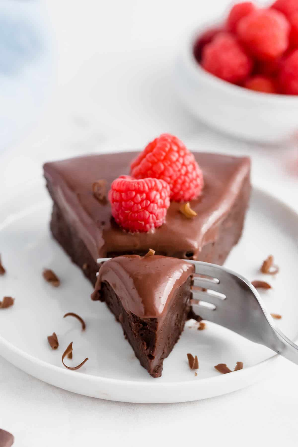 a fork taking a bite out of a slice of flourless chocolate cake