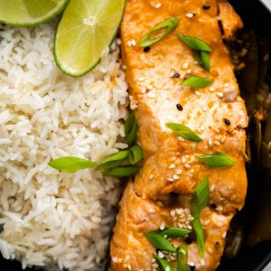 a slice of cooked sesame salmon on a plate with rice