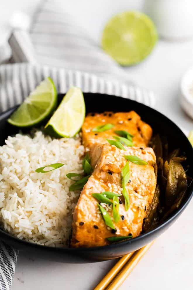 a slice of salmon sitting in a black plate with rice and lime wedges