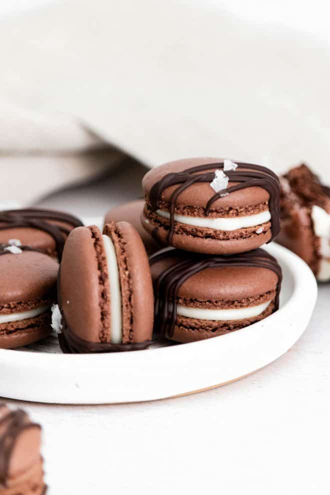 a stack of chocolate macarons sitting on a white plate