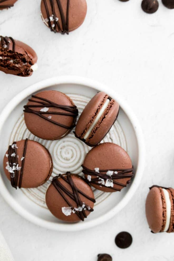 five chocolate macarons sitting in a circle on a white plate