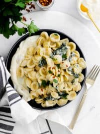 a plate with whipped ricotta and pasta with kale