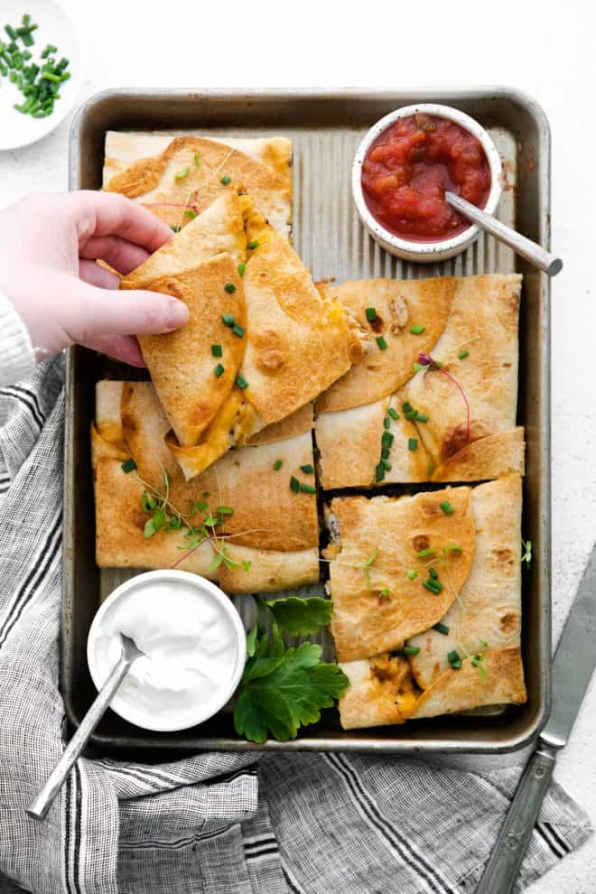sheet pan quesadillas on a pan with sour cream and salsa