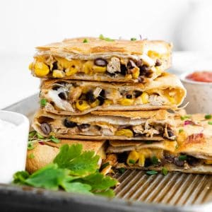 a stack of four pieces of sheet pan quesadillas sitting on a pan