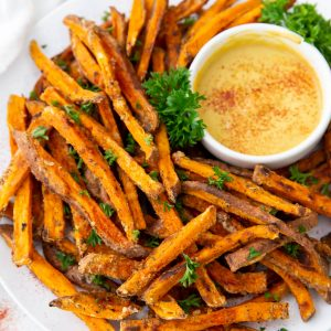A plate of sweet potato fries with sauce