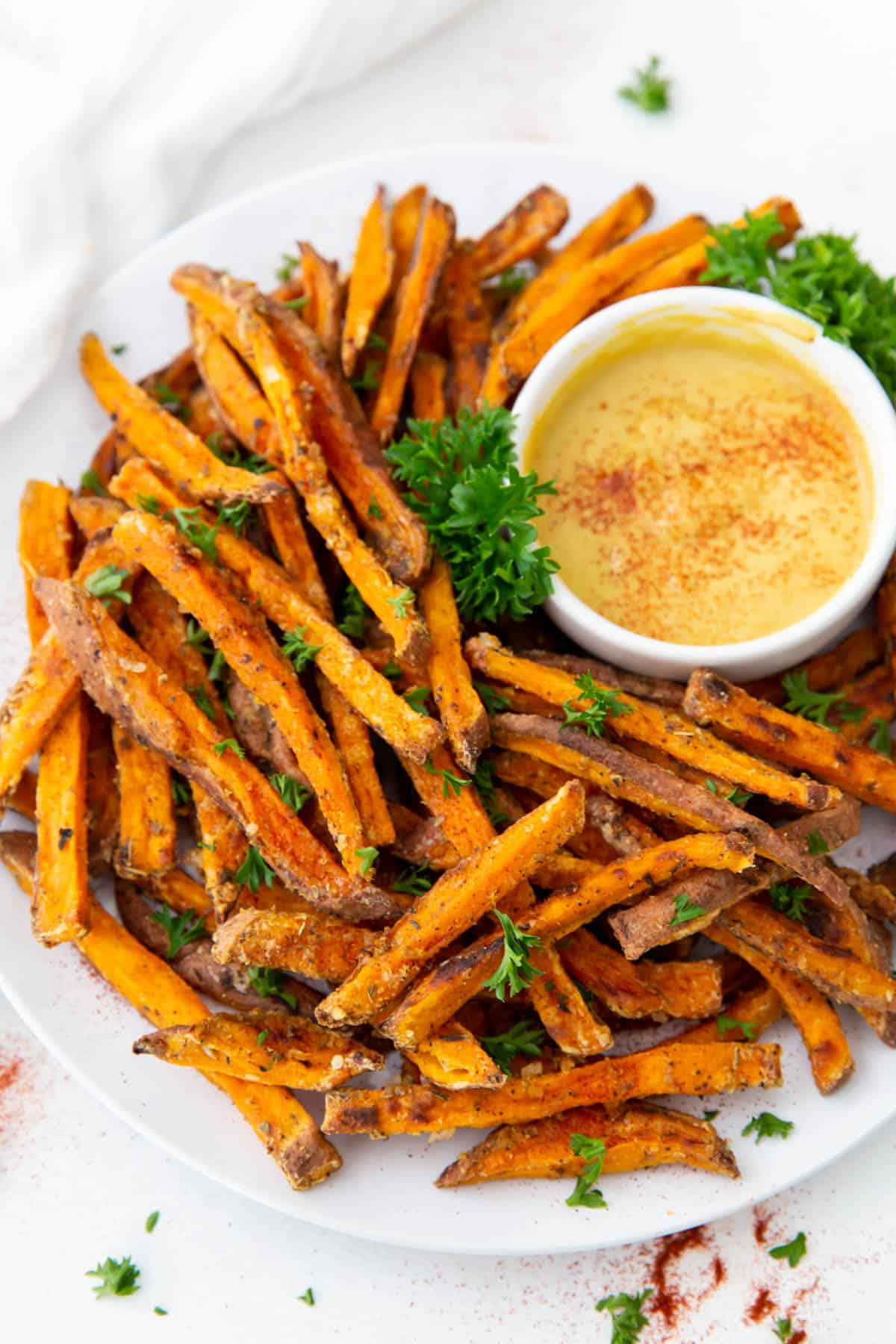 A large plate of fresh sweet potato fries on a white plate garnished with parsley and a small white bowl of mustard for dipping.