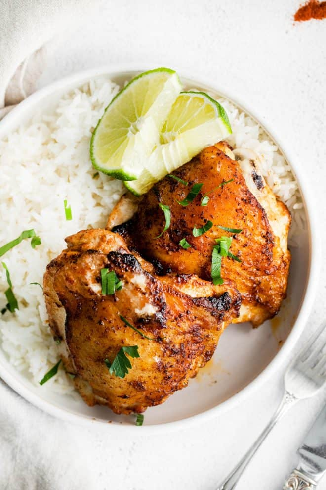 two chicken thighs on a plate with a side of rice and lime slices