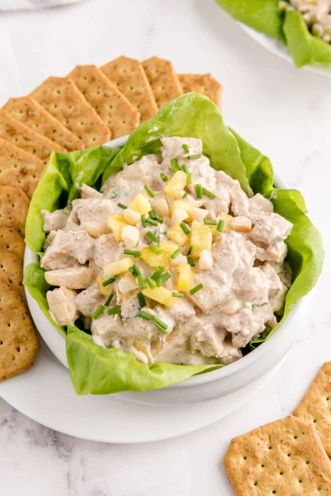 a bowl filled with hawaiian chicken salad with crackers