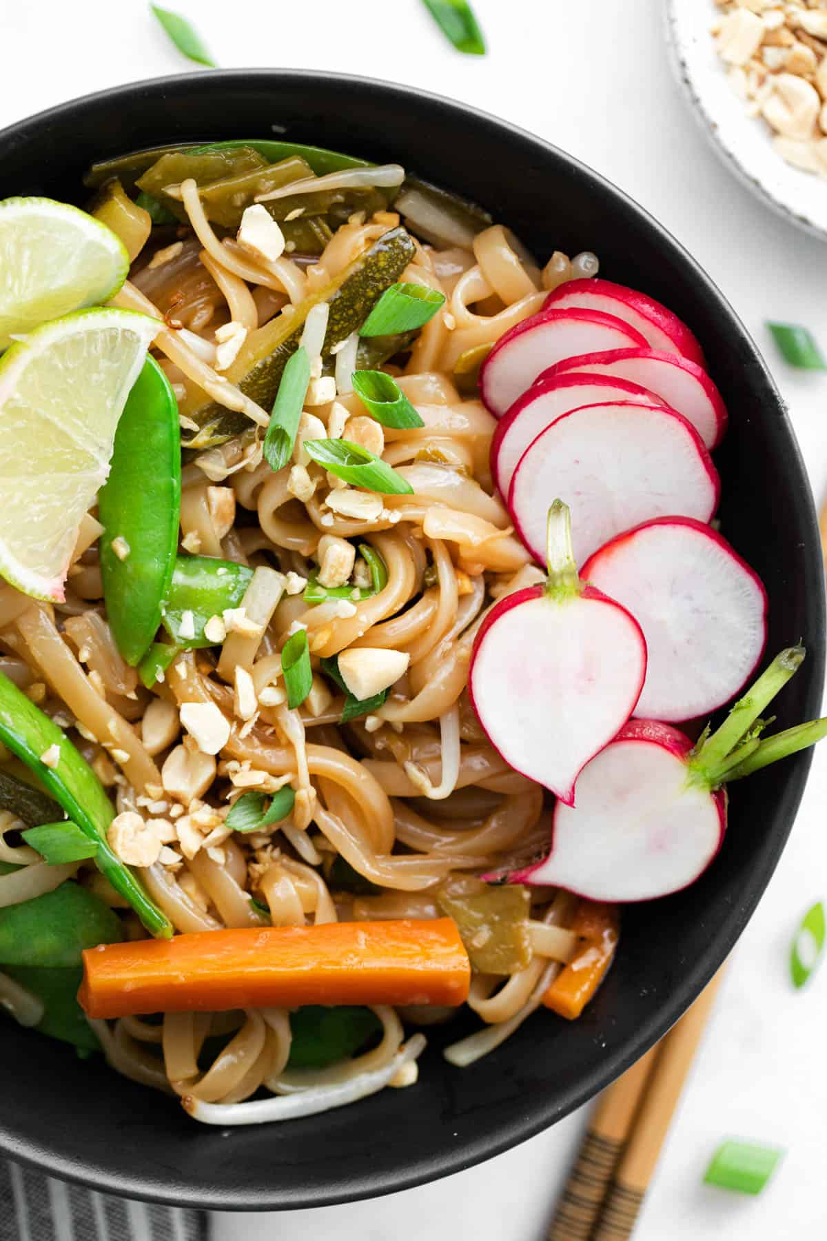 A close-up of a bowl of vegetarian pad thai with noodles with noodles, snow peas, green onions, carrots, radish and lime.