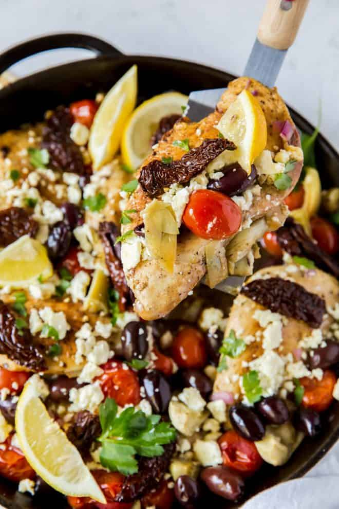a piece of mediterranean chicken in a skillet with toppings