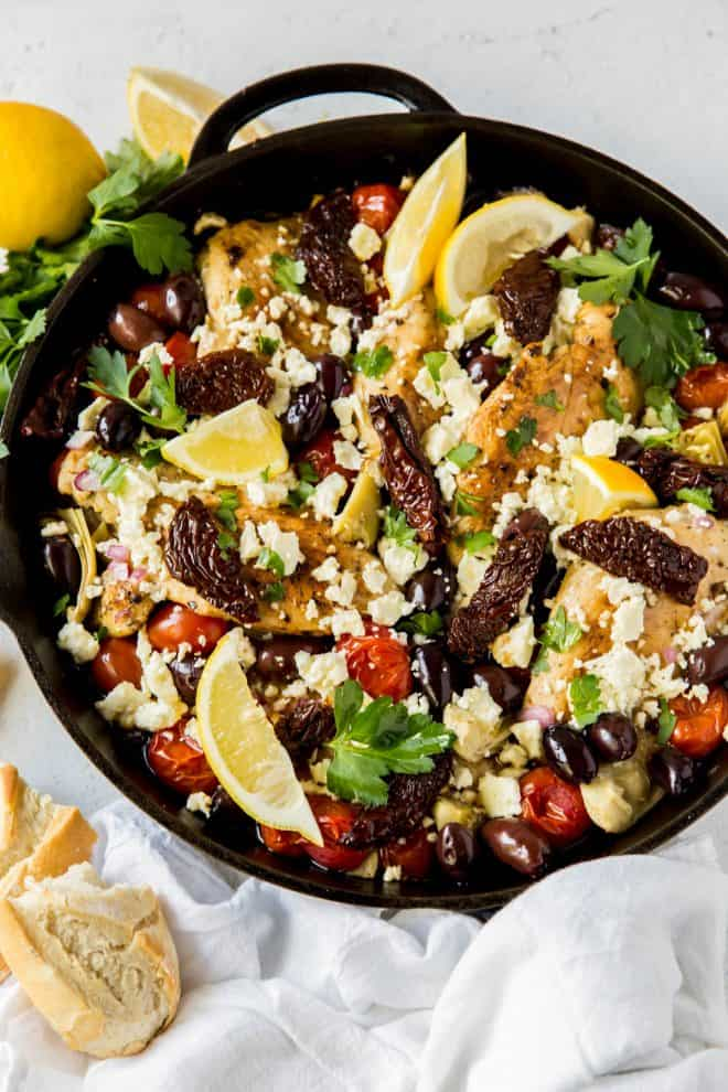 cooked mediterranean chicken in a skillet with artichokes, olives and tomatoes