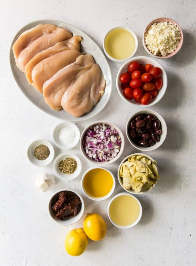 ingredients for mediterranean chicken in bowls on a white table
