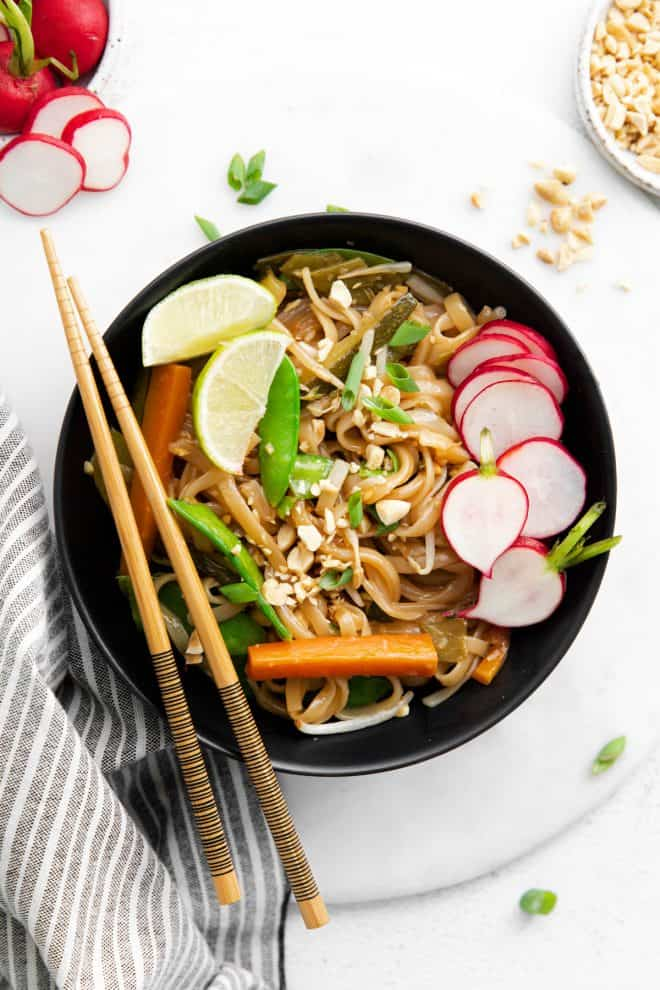 A bowl of vegetarian pad thai garnished with radish and lime, and a pair of chopsticks laying across the bowl.