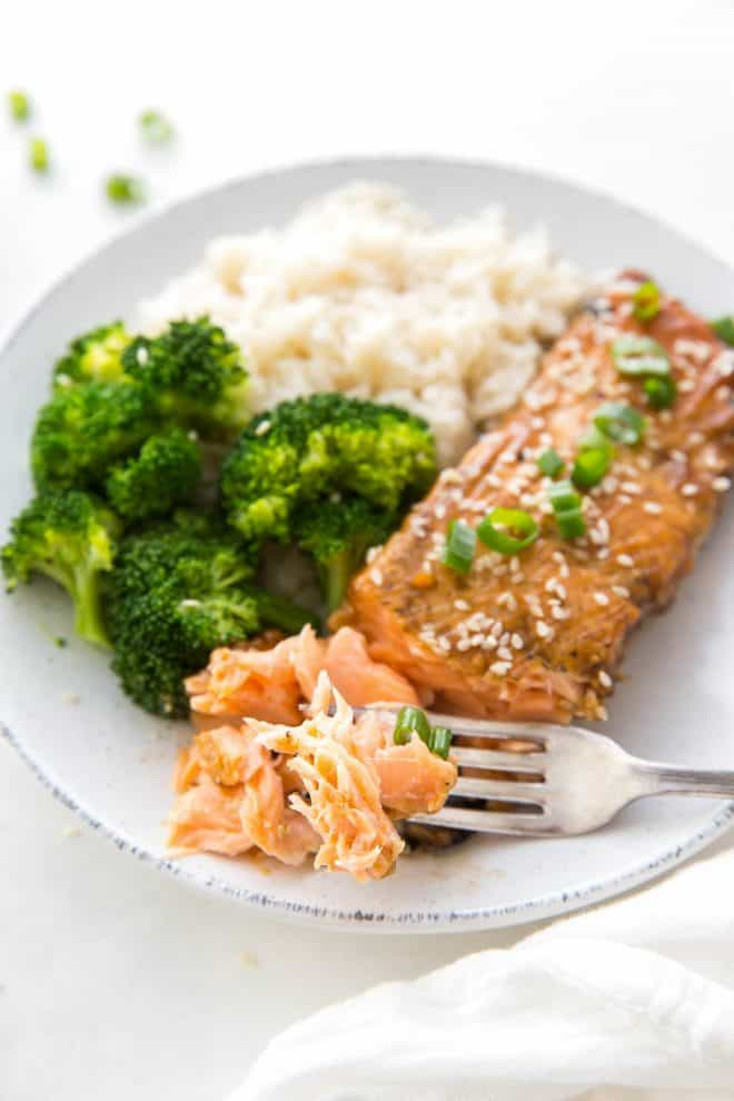 A fork with flaky salmon, on a plate with a salmon fillet, broccoli and rice.